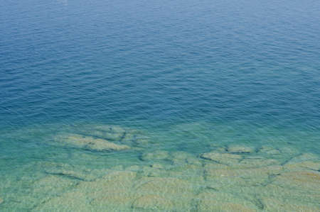 Rippled pattern background of clean and transparent water in Garda Lake, Northern Italy
