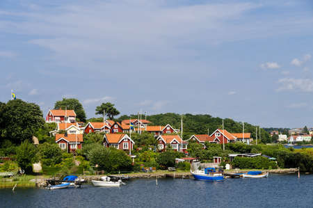 Swedish cottages on the sea painted in the typical  Falun red  color in Br�ndaholm, Karlskrona county, Sweden
