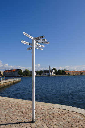 A white signpost in Karlskrona harbor, Sweden, showing distances to some of the most important cities of the Baltic Sea