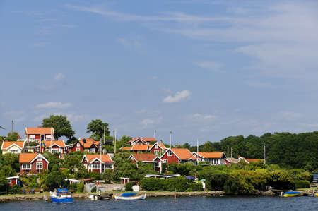 Swedish cottages on the sea painted in the typical  Falun red  color in Br�ndaholm, Karlskrona county, Sweden photo