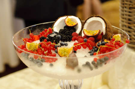 A big glass with ice and fruits  berries, passion fruit, coconut  photo