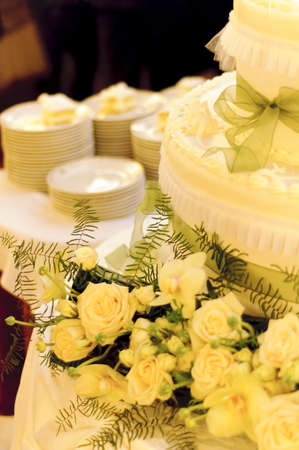 Yellow cream wedding cake with green ribbons decorated with yellow roses