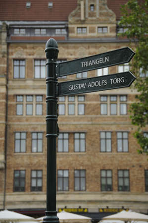Iron signpost in Malmo, Sweden, giving directions for two of the landmarks of the town  Triangeln and Gustav Adolfs Torg