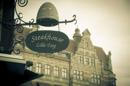 lilla: Malmo, Sweden - August 2010: Vintage photo of an iron shop sign on an historic building in Lilla Torget in Malmo, Sweden, with an old historic palace in the background Editorial