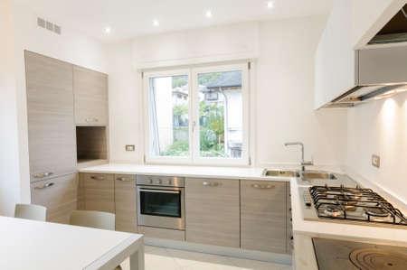 Moderne Küche Interieur mit Holzgehäuse und weißen Tisch