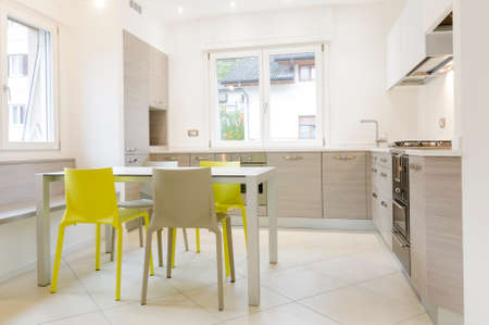 Modern kitchen interior with wooden cabinets, white table, grey and yellow chairs