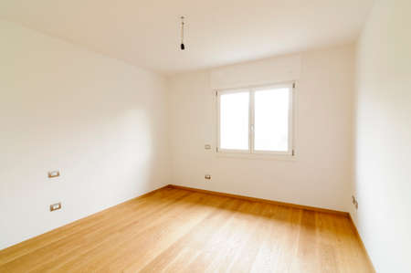 Spacious empty room with white walls, window and parquet floor photo