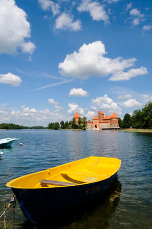 A yellow boat with the castle of Trakai in the background Lithiania