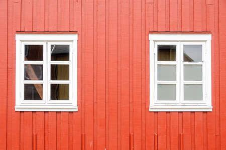 Red wall and white windows of a traditional wooden rorbu in the Lofoten Islands, Norway, Europe