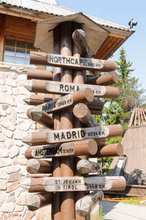 A wooden signpost in Santa Claus Village, Rovaniemi, Lapland, Finland showing distances of some of the most important European cities from the Arctic Circle