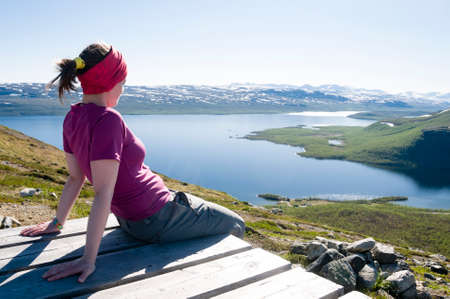 Girl sitting on the top of Saana Fell and looking down at Lake Kilpisjarvi and surrounding area. Kilpisjarvi, Finnish Lapland, Finland, Europe Stock Photo