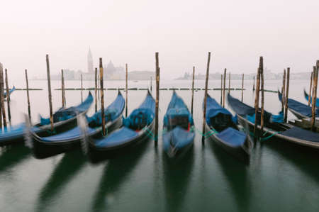 Gondolas, the traditional flat-bottomed Venetian rowing boats, at their moorings in San Marco Square at sunrise, with the lagoon and the church of San Giorgio Maggiore in the background, Venice, Veneto, Italy, Europe (intentional motion blur)