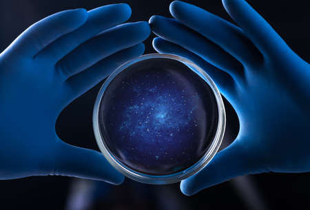 Doctor hand holds petri dish with galaxy