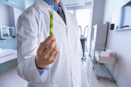 Doctor with medical tube on hospital background