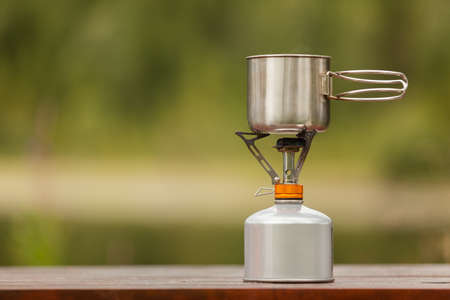 The camping iron mug with a gas burner on natural bokeh background 免版税图像