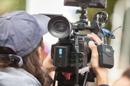 Man journalist with a modern large black video camera on bokeh background