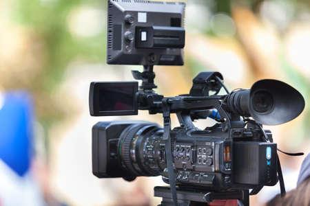 Periodista hombre con una moderna cámara de vídeo negra grande sobre fondo bokeh