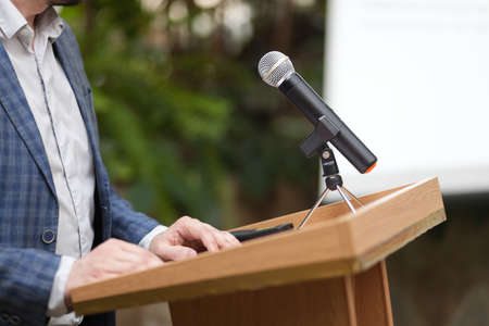 A man stands behind a stand with a microphone and holds a conference