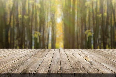Wooden desk on autumn blur natural background