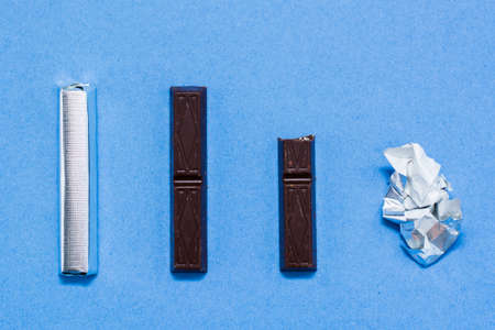 Chocolate life cycle from whole packaged to empty wrapper on blue cardboard background concept
