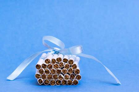 A stack of new thin cigarettes is tied with a blue ribbon with a bow lying on a blue background. The danger of smoking for women. Fatal addiction.