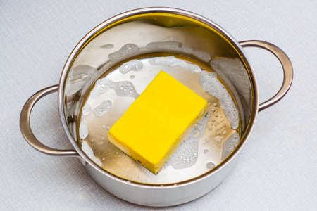 The yellow dishwashing sponge lies at the bottom of the soaped pan on the table.