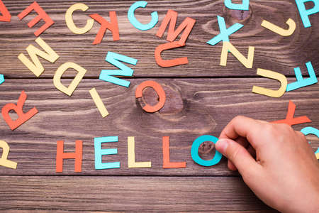 """Children`s hands make up the word """"hello"""" from colored carved cardboard letters on a wooden background. Top view"""