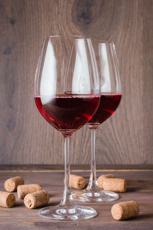 Two glasses with red wine and cork on a wooden table