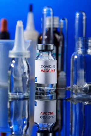 covid vaccine glass fillet with syringe and other laboratory containers placed on reflective surface, isolated on blue background