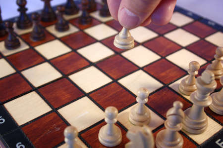 first move: Chess pieces on a chessboard, the first move Stock Photo