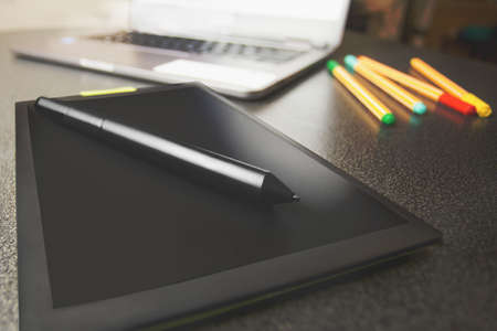 Top view of a modern graphics tablet isolated on a black background, pen for working with graphics on special equipment to help with computer work, innovation 2020
