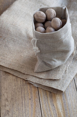 Walnuts in a cotton bag on a wooden table covered with burlap. Stock Photo