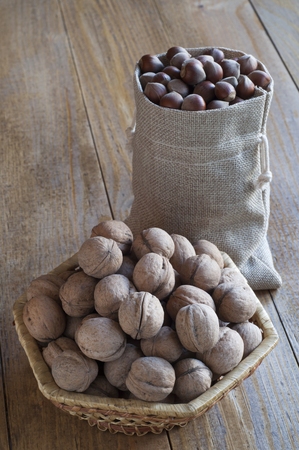Hazelnuts in a cotton bag and walnuts in a wicker basket on a wooden table.