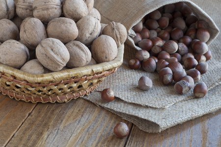 Walnuts in a cotton bag and hazelnuts in a wicker basket on a wooden table covered with burlap. photo