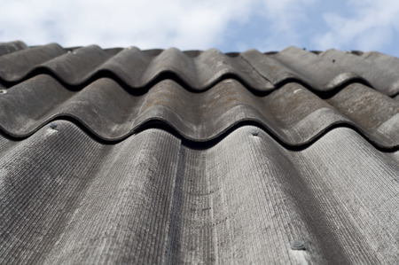 slate roof: Old slate roof and blue sky. Vertical image.