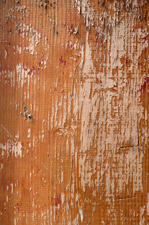 spall: Wooden surface with an old paint peeling brown. Vertical image.