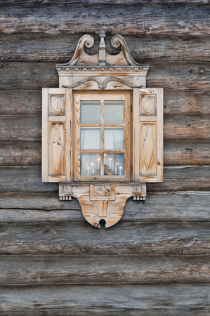 Window with carved architraves in a wooden hut.