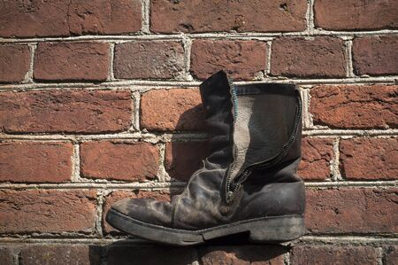 Old seedy boots on the background wall of red brick. Boots in the center of the image. 스톡 콘텐츠