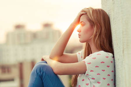 fille triste: belle jeune fille solitaire assis sur le toit Banque d'images