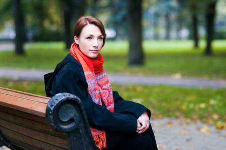 beautiful girl sitting on a bench in the park in autumn photo