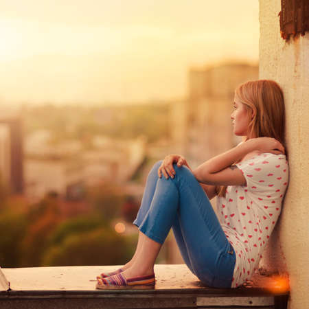 mirada triste: hermosa rubia sentado en el techo de la casa