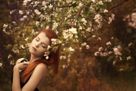 beautiful redheaded woman in a spring garden photo