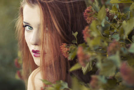 Beautiful redhead young woman in park photo