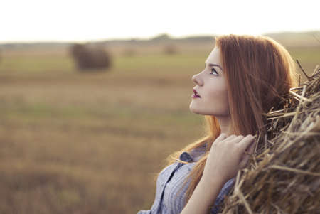 hay field: portrait of a beautiful red-haired girl in a field