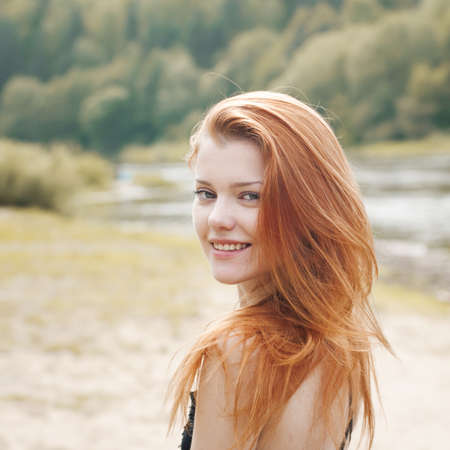 nude outdoors: portrait of a beautiful red-haired girl