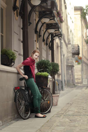 beautiful girl with a bicycle on the streets of the beautiful city photo
