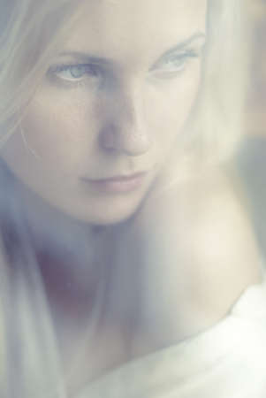 portrait of a beautiful blonde through the glass Stock Photo