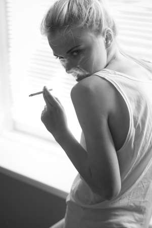 beautiful young woman smokes at home by the window photo