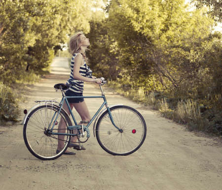 beautiful smiling girl with a bicycle on the road photo