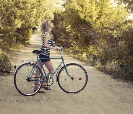 bicicleta retro: hermosa ni�a sonriente con una bicicleta en la carretera